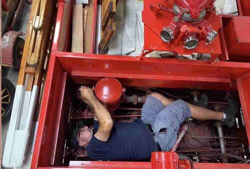 Los Angeles County VP Joe Woyjeck lying on the top of the pump working on Engine 51 (Ward La France)