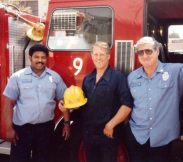 Three Firefighters standing in front of the driver's door of Engine 9. Firefighter Anthony Jefferson, Engineer Jimmy Howe & Captain Emmet Kinney